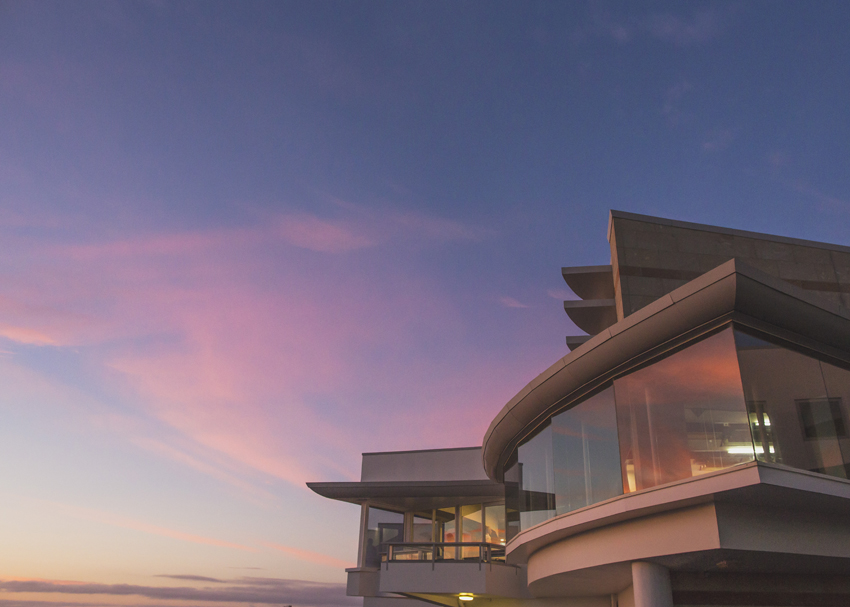 A pink sunrise reflecting of the windows of the Napier Conference Centre